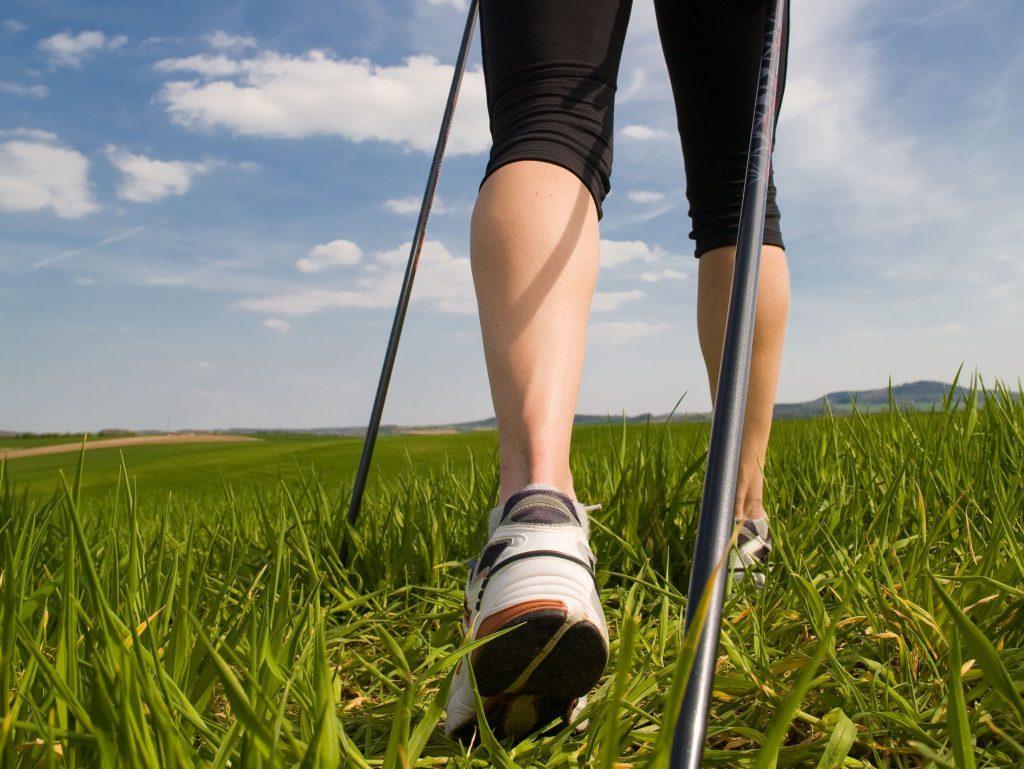 Gambe femminili in un prato con bastoni da Nord walking