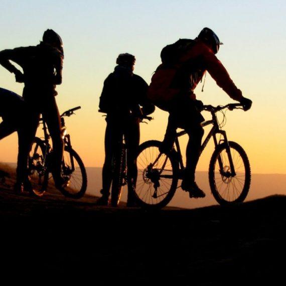 Quattro persone in bicicletta al tramonto